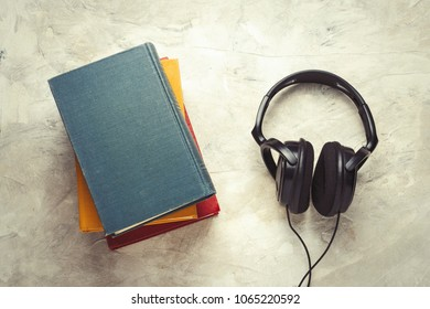 Books and Headphones on a white stone background. Concept Audiobooks.