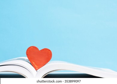 Books and heart shape wooden piece.