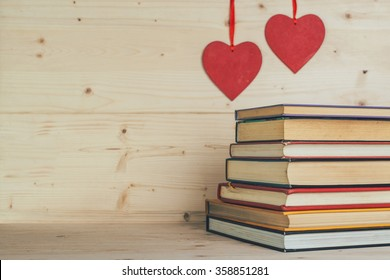 Books and hearts on a wooden background