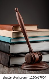 Books and a judge's gavel on wooden table. Juridical science and legal studies concept.