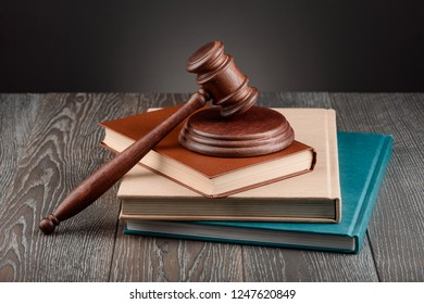 Books, a judge's gavel and a sound block on wooden table. Learning jurisprudence, juridical concept.