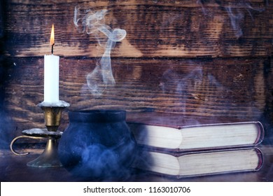 Books of magic and witch pot with smoke and candle burning in candlestick. Old wooden background. Halloween concept. Close up, selective focus