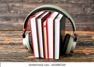 Books and modern headphones on wooden table. Concept of audiobook