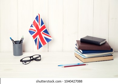 Books, notebooks, glasses and the Great Britain flag on the desk. English language learning.