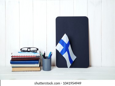 Books, notebooks, textbooks, glasses, a flag of Finland on a wooden table. Education in Finland.