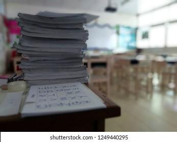 Books o paperwork piled up on a teacher's desk in a school classroom