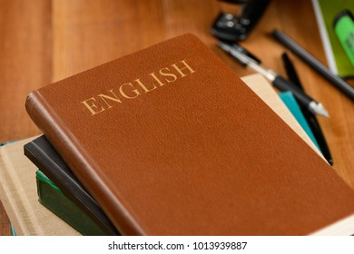 Books and office products on wooden desktop. English school book, brown leather. Education concept.
