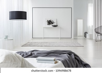 Books on bed with grey blanket in spacious bedroom interior with black and white poster on the wall