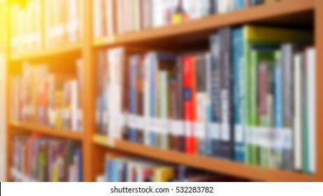 Books on bookshelf in library room blurred focus for education background