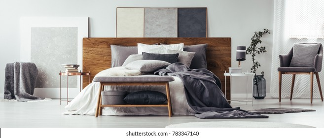 Books on copper table and bench next to bed with wooden bedhead in modern bedroom interior with grey chair