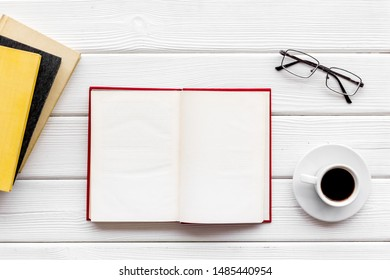 Books on library desk for reading, coffee, glasses on white wooden background top view mockup