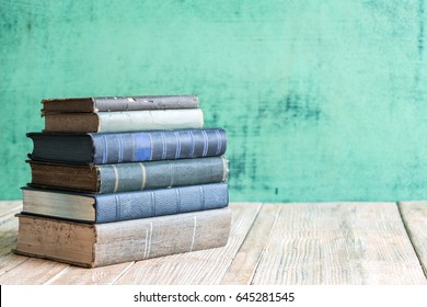 Books on the old Wooden table background.
