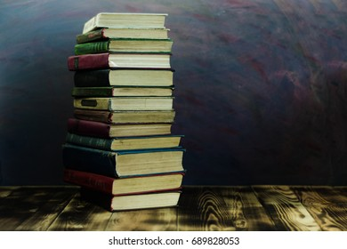 Books on an old wooden table. Beautiful dark background.