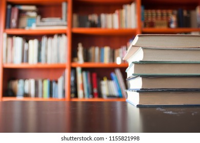 books on the table in front of the red wooden library