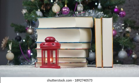 Books on the table and a red lighted lantern.
