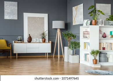 Books on white bookshelf and plants in floral grey living room interior with paintings on the wall