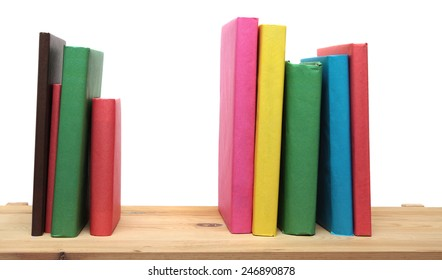 Books on wooden shelf close-up isolated on white background. No labels, blank spine.