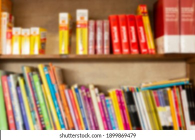 Books are on a wooden shelf. Education and training. Blurred.