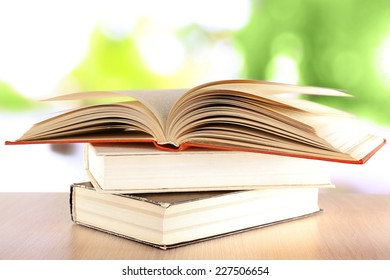 Books on wooden table on natural background