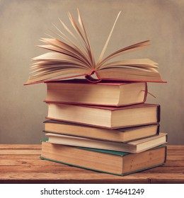 Books on wooden table over vintage background