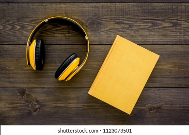 Books online concept, audiobooks. Spend leasure time reading and listening music. Headphones near hardback book with empty cover on dark wooden background top view