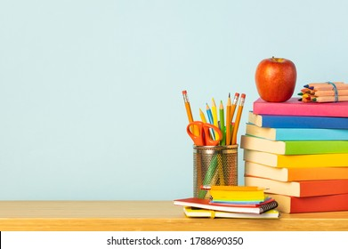 Books and pencil holder on school desk. Back to school concept.