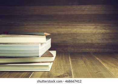 Books and pencil on wood table and background, selective focus