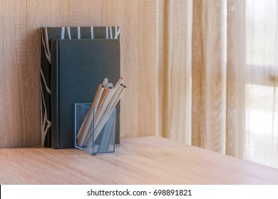 Books and pencils on bookshelves.