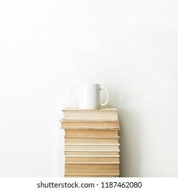 Books pile and coffee mug on white background. Minimal education concept.
