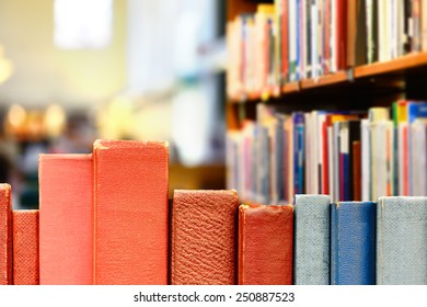 Books in row, library shelves in background
