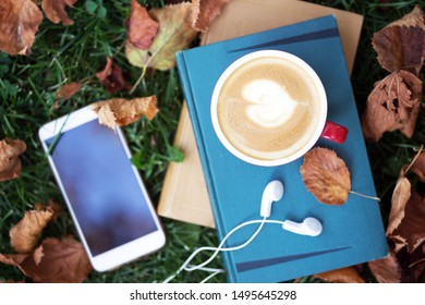 books, smartphone, earphones and cup of coffee on grass. fall and relax