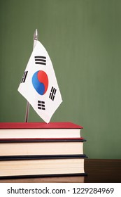 Books and South Korea flag in front of a green chalkboard