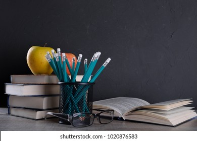 Books in stack apple and pencils in metal holder pot on wooden table in front of wall - Shutterstock ID 1020876583