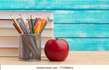 Books stack and school supplies on wooden table