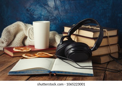 Books are stacked, Headphones, White Cup, Orange Slices, open Diary on a wooden background. The Concept of Audio Books and Audio Education.