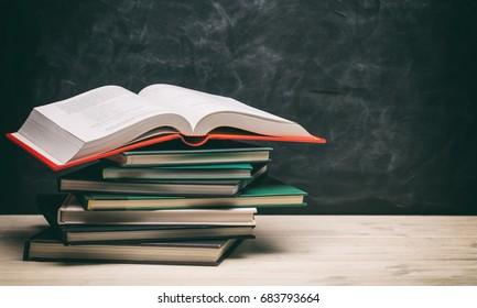 Books stacks on blackboard background - copy space