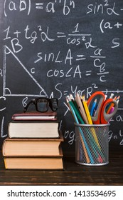 Books and stand for pens on wooden table, against the background of a chalk board with formulas. Teacher's day concept and back to school.