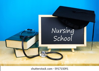 books, stethoscope and blackboard with text nursing school on wooden background.