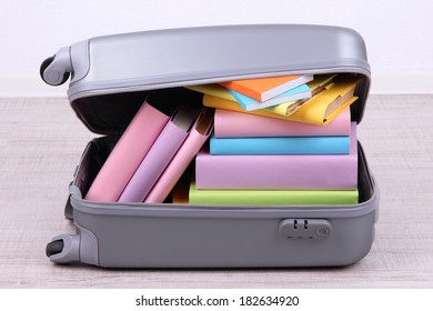 Books in suitcase on wall background