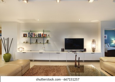 Books and television in living room, comfortable furniture and designs, walls are white color, chairs around the tables, inside rooms of a apartment.