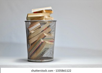 books in trash basket