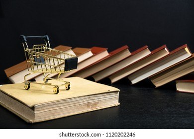 Books with trolley symbol of bookshop. Stack of old books on a wooden shelf and shopping carts