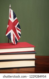 Books and UK flag in front of a green chalkboard