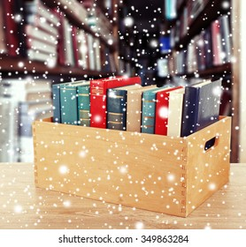 Books in wooden crate on bookshelves background over snow effect