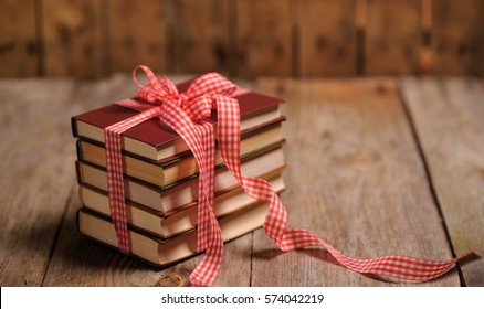 Books wrapped with color ribbon, on wooden table