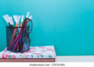 Books,glasses and colorful pens on wooden table with copy space.Green background.