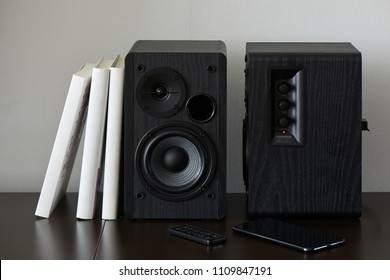 bookshelf speaker with books, smartphone and remote controller on a TV stand