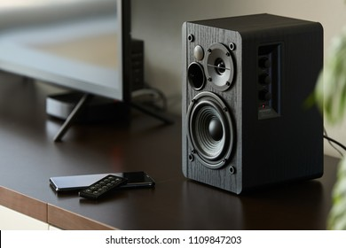bookshelf speaker with remote controller and smartphone on a TV stand