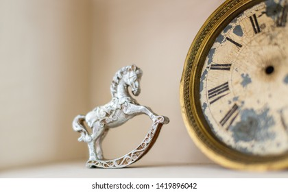 Bookshelf with vintage objects - old fashioned figure of rocking horse and retro clocks.