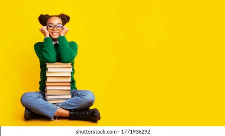 Bookworm. Dreamy afro teenage girl sitting on floor with pile of books over yellow background, copyspace, panorama